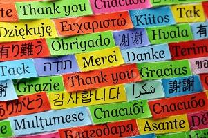 Palabra gracias escrita en papeles de muchos colores en muchos lenguajes diferentes.